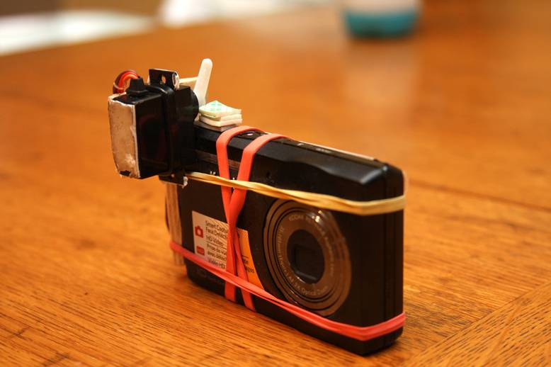 I used nothing but rubber bands to hold the servo and wood to the camera.  This way, I can easily take it off or make adjustments.