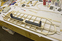 """Name: Wing Building 3.jpg Views: 26 Size: 405.3 KB Description: Trailing edge shows gradual shims from mid-panel increasing to 1/4"""" at tip. Net washout after covering 3/16"""". Leading edge shimmed up in place in front of ribs, prepared for gluing. Wax paper will go under ribs first."""