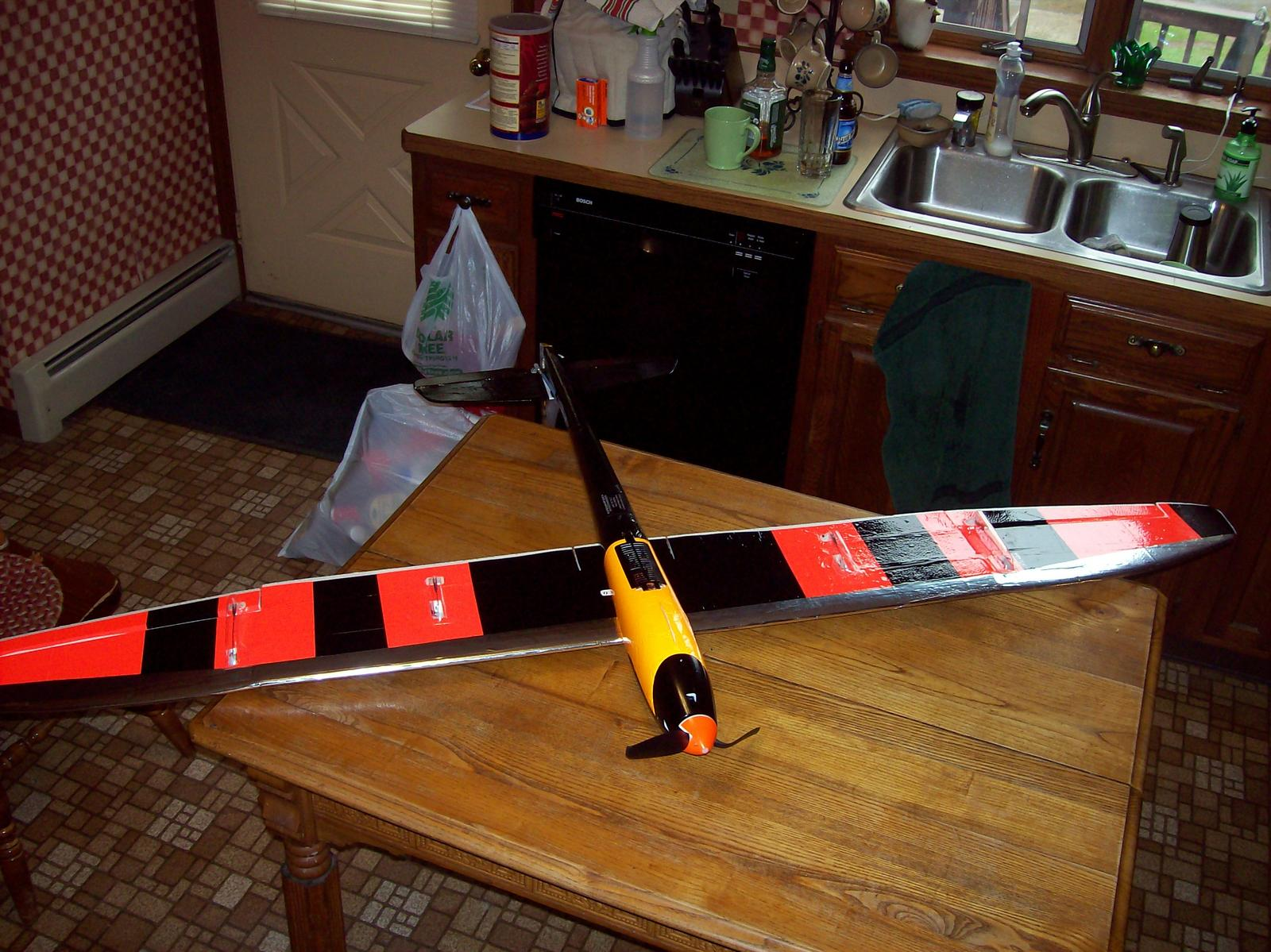 Belly view showing florescent red trim sheeting and Econocoat black stripes on bottom of wing, Econocoat black for tail boom and bottom of tail group, florescent orange trim sheeting for center of fuse, glossy black spray paint for plastic cowling, flores