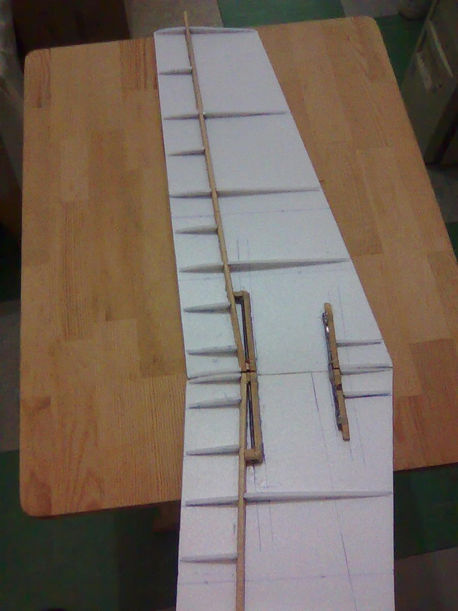 This is a 2-piece wing. They are connected by 2mm piano wires and a rubber band under the bottom. The two short spars are for glueing plastic tubes for insertting the piano wires. The airfoil is as thick as 18mm, a thinner clark Y one.