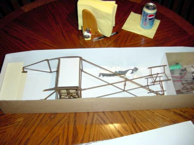 Under the wings is the fuselage secured in place by cardboard with other parts bagged and stored to the right.
