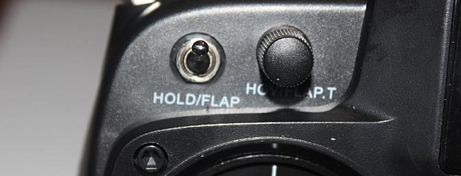 The THROTTLE HOLD/GEAR switch is located on the top left front of the transmitter