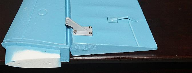 The rudder control horn with the four screws inserted.