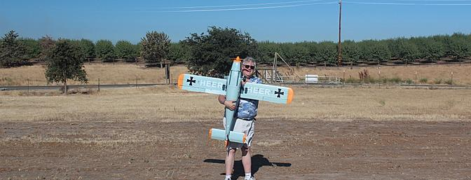 Author holding his plane. Gives a size comparison as I am 6 feet tall and lets me show off my name on the underside of the wings.