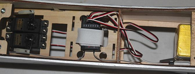 The receiver installed with straps between the servos and the battery tray.