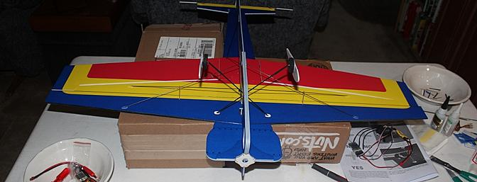 The plane is placed upside down for attaching the aileron servo and control rods.