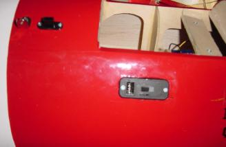 On/off switch in center with receiver battery charging jack. Upper left is the plug for aileron extension wire.