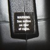 The transmitter charging jack is behind this sticker. the stickers warn not to use with Alkaline batteries.