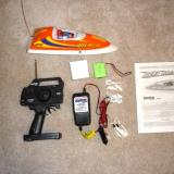 Every thing that comes with the Reef Racer: boat, battery, charger, transmitter, instructions, two extra fuses and a spare prop.