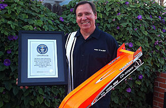 "Nic Case photographed with the ""R/C Bullet"" and the Guinness World Record certificate for the Fastest Battery-Powered RC Car."