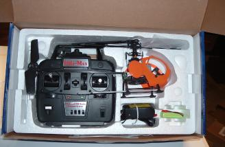 The Heli-Max RotoFly is packaged with a transmitter, battery, charger, and training gear.