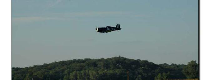 The F4-U Corsair with the corn and ridgeline in the background.