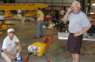 The man who makes it all happen...Pat Hartness (right)...poses with his electrified extra in the hangar.