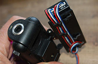 The camera module bracket has clips for wires and is adjustable.