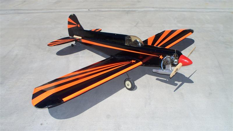 I rather like the black and day-glo orangey-red color scheme.  Won't be a problem seeing this thing in the air!  The trim is actually more bright orange than it appears to be in the photo.  Reminds me of the Batmobile.