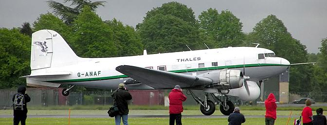 Douglas DC-3 (G-ANAF) of the Air Atlantique Historic Flight at Hullavington Airfield, Wiltshire, England, taking off.  The aircraft is operated by Air Atlantique on behalf of Thales Group for development of the Nimrod radar. The radome under the cockpit contains a rotating parabolic antenna. A new pitot tube was fitted to the nose (the original tube under the nose would interfere with the radar). The APU behind the starboard wing provides electrical power for the radar systems. Note the added vertical stabilizer behind the tail wheel. The aircraft was built in 1944 and apparently operated as part of the Berlin airlift.  Photographed by Adrian Pingstone in May 2005 and placed in the public domain.  Retrieved from Wikimedia Commons.