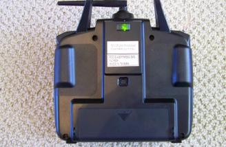The rear of the transmitter shows the green LED indicating transmission.