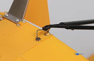 Slip base of strut over brass fitting on fuselage.