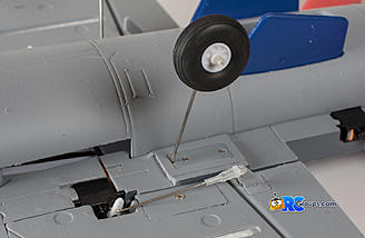 The wire landing gear installs with 2 screws each. It is easier if you install these prior to gluing the vertical fin in place