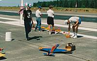 Name: F1 at Whidbey Island NAS.jpg Views: 560 Size: 83.9 KB Description: Ready station for the next heat at Whidbey Island NAS. Brian Richmond, Darrol Cady & Tom Strom. Bob Hunt is walking by with his model. The black rubber on the runway is from naval jets performing touch and goes.
