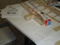Name: front fuse.jpg Views: 360 Size: 50.4 KB Description: Fuse held together by hobby-knife tourniquet and sandblock.  Wax paper box provides balance.  Enough compression to hold bond, hopefully not too much to crunch.  Note scraps of balsa on floor for future reinforcement.