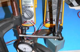 This mess actually does something.  The multimeters are used to measure the current and voltage supplied to the servo.  The dial indicator allows me to measure the position of the servo horn.