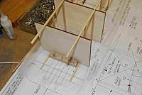 """Name: FuseFrame04A.jpg Views: 213 Size: 133.3 KB Description: After framing ea fuse side, I made a couple of lt ply squares w/ notches cut in to accomodate to keep the fuse straight in all axes while I applied the cross members.  These rest flat on the board and are pinned thereto.  Alternatively, external """"L's"""