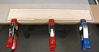 Name: 46-Setup for cutting nose planking.jpg Views: 410 Size: 129.9 KB Description: Setup for cutting nose planking: MDF or countertop, plastic cutting mat, balsa, template and however many clamps to secure (I say that a lot, don't I?). I freehand cut the angle with the bevel away from the template (see photo above).