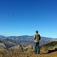 Name: 20161116_141534_resized.jpg Views: 28 Size: 495.4 KB Description: Glenn and his Espresso in the distance.  The latest wildfire bulldozered contingency line really dug up the landing spot and actually changed the slope in the lower saddle.