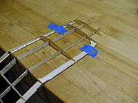 Name: SpookE 13.jpg Views: 72 Size: 60.9 KB Description: Full ribs added in the outer portion of the wing.  Note the tape holding the panel flat on the bench.  Be careful not to bump the part of the wing off the bench!