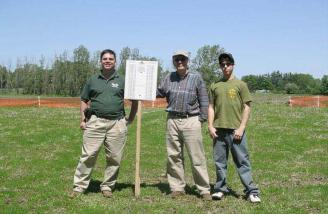 By the end of May 2004, the weather was improving. Here members Jim Connell, Gordon Braun-Woodbury and instructor Adam Rogozinsky stand next to our new frequency board.