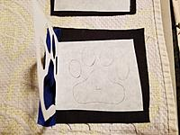 Name: BC Logo 3.jpg Views: 7 Size: 3.46 MB Description: Time to cut out the pads of the paw.   The master blank is moved to the sail to line up the pads of the paw.  The paper is removed from back of the Heat n Bond and the pads are ironed to the sail using the master blank.