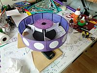 Name: IMG_20180725_200820_01.jpg Views: 24 Size: 299.4 KB Description: This was the last tail ring I made (different blimp).  Using balsa and tissue this time.  Threads on the back edge act like bicycle spokes to keep the shape.  The front side has three mounting points.  Here, attached to an alignment jig.