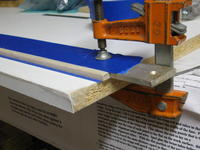 """Name: IMG_0429.jpg Views: 181 Size: 76.0 KB Description: Leading edge stuck to aluminum bar straight edge with blue tape underneath, 1/16th"""" overlap of blue tape on top for sanding protection stop."""