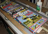 Name: StellarPete31.JPG Views: 10 Size: 590.4 KB Description: Gluing the leading edge top sheeting. Model magazines (or at least aviation mags) make an excellent conformable weight. Do not use fashion or cooking mags, lest your aircraft turn floral pink and sink like a sad souffle.