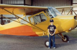 A sharp-looking young man beside a good-looking airplane.  Me beside Dad's Champ in Enterprise, AL, ca. 1981.