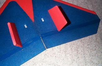 I chose to cut rectangular holes in the wing and leave the servos upright.
