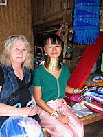 Name: .jpg Views: 75 Size: 187.7 KB Description: My wife with one of the Burmese Long Neck women.  (Those brass rings weight about 30 pounds, and her neck will eventually be nearly a foot long by the time she is old, if she lives that long.
