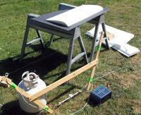 Name: hot_wire_cutting.jpg Views: 390 Size: 103.0 KB Description: my hot wire setup, about as simple as it gets: sawhorses, piece of slate, wooden bow, and steel fishing line for the wire connected directly to a 12V battery charger.