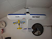 Name: DSC01382.jpg Views: 66 Size: 120.9 KB Description: Super Cub mounted in the basement next to the UM Sukhoi XP. I have yet to maiden the SC. Added larger wheels fitted with shrinktubing. These are for next season.