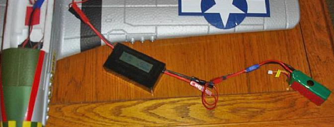 The battery supplies power through a series of connectors through the watt meter to the motor.