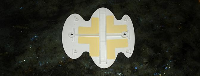 The plastic wing center cover mount with the 4 -L shaped two sided pieces of tape installed in it.
