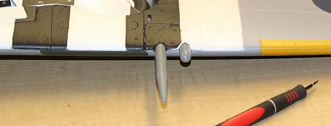 The gun covers glued back in place to complete the plane's assembly.