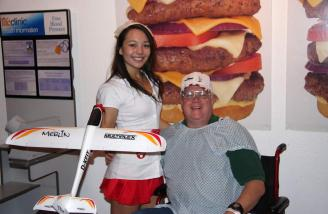 Author with nurse who is holding his Merlin at the Heart Attack Grill, Chandler, Arizona.