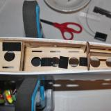 The battery compartment with hook and loop material glued to the wood.