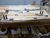 Name: 6.jpg Views: 109 Size: 217.6 KB Description: Fuselage side laminations coming along, with a number of die cut parts and doublers added.  Also epoxied in the crutches and blocks