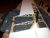 Name: 100_4434.JPG Views: 15 Size: 137.8 KB Description: The custom made carbon junction ready to be inserted in the wing spar openings. Trailing edges already partly glued and junction reinforcements in place to be slided into the remains, balsa nose fairings glued on top and bottom of leading edge plywood