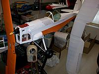 white and orange Oratex applied to the model, cockpit cover screwed on fuselage, forward and aft canopy rake glued to fuselage, as well as oil tank, landing gear mounted and nose compartment plus accessories in white primer, nose covers still natural