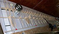 Name: 100_5124c.jpg Views: 31 Size: 429.9 KB Description: All ribs glued to the lower main and aft spars, trailing-edge supported by the custom tapering support. Long spars kept straight by pins where necessary