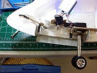 Name: fuselage_27.jpg Views: 130 Size: 162.1 KB Description: Same shot with gear down, forward spring pulls plate down to push and keep the door open, aft springs now under tension to ensure precise steering whilst allowing incidental shock absorptions.